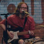 One-man band Mike Hosty sings while playing drums and guitar during this Play It Loud webisode.