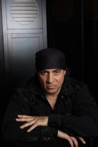 Steven Van Zandt sits for a publicity photo in front of a set of lockers, wearing his trademark black bandanna, sitting with his arms crossed