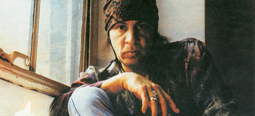 Musician Steven Van Zandt sits for a portrait next to a window in what looks to be a loft.