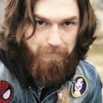 Caleb Starr portrait as he sits on a picnic table, wearing a jean jacket with various iron-on patches, hands in pockets, and looks at the camera.