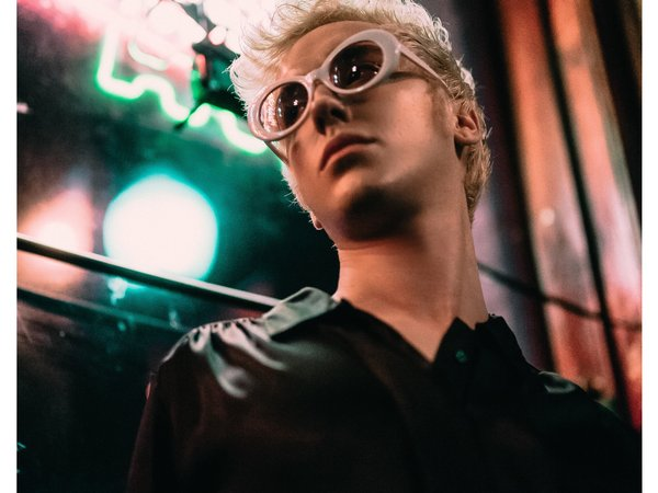 ACM@UCO alumnus Harlee Lane poses in front of neon lighting at night as he poses with oversized white sunglasses, black button-up shirt and short, platinum hair.
