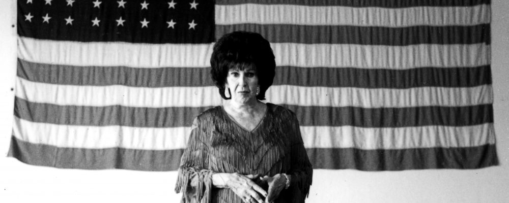 Longtime musician and performer Wanda Jackson poses in a fringe top, standing in front of an American flag, in this undated publicity photo.
