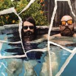 Colourmusic members Ryan Hendrix and Nicholas Ley sit in a swimming pool, wearing sunglasses