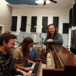 musician sam weber leans on a piano as two musicians next to him play piano in a music recording studio