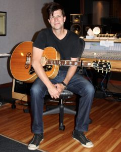 Zac Maloy sits in a recording studio, smiling, with an acoustic guitar in his lap as he smiles at the camera.