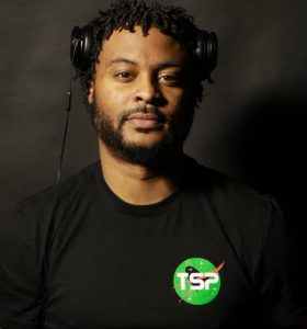 Stevie Johnson, aka DJ and producer Dr. View, stands with his headphones pulled above his ears as he looks at the camera in this color portrait.