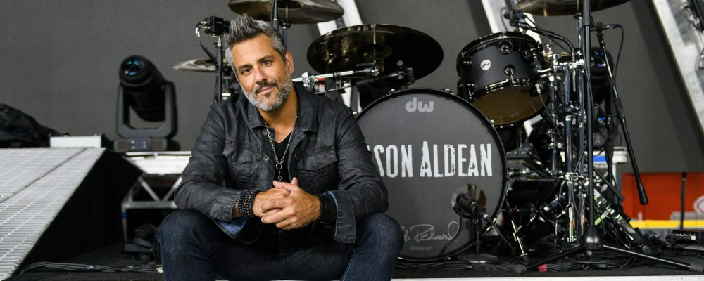 Drummer Rich Redmond, dressed in black, sits on a riser with his drum kit behind him, which he uses when he tours with country music star Jason Aldean