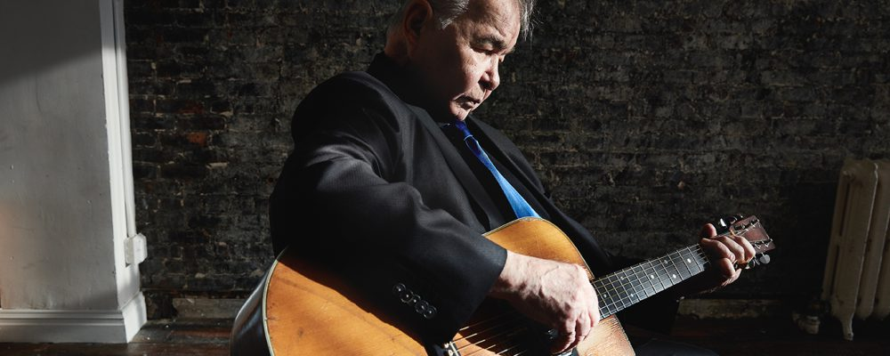 A portrait of musician John Prine playing guitar. He's dressed in a dark blazer holding a wood-topped hollow-body acoustic guitar.