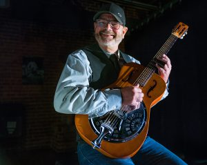 Guitarist Danny Hargis poses with a steel guitar in this candid portrait. He's wearing a denim shirt, vest, jeans and baseball cap.