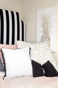 photo of headboard with black and white stripes, with pillows in front and pineapple wall on the adjacent wall