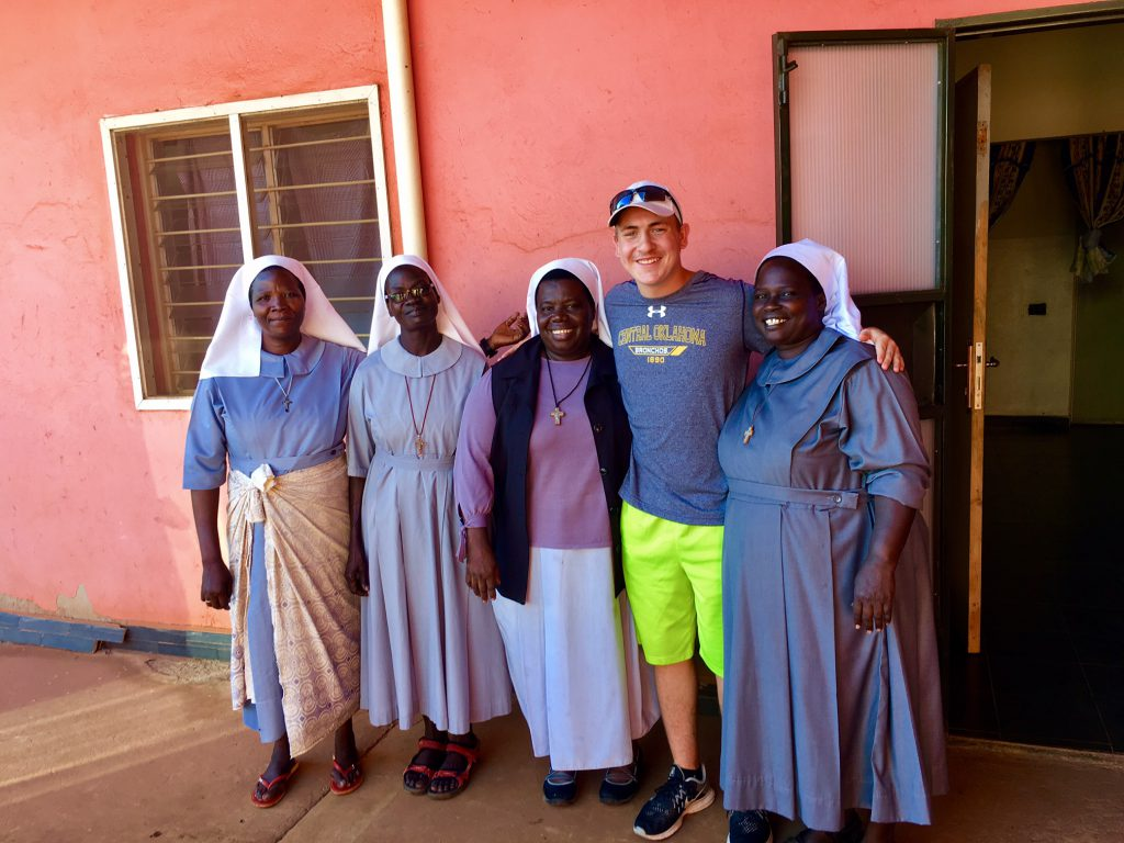 Four women at St. Monica's convent in Uganda stand with student Stockton Duvall.