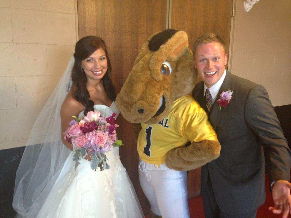 A bride and groom pose with Buddy Broncho at their wedding.