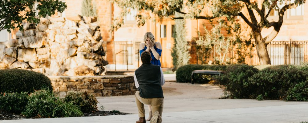 A man proposing to a woman in front of Old North.
