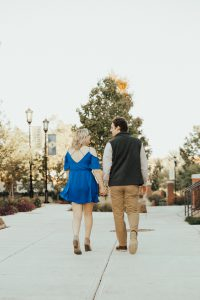 A woman and a man walk away from the camera, holding hands.