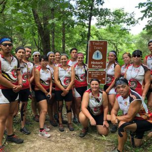 a group of bike riders poses in front of a sign on the trail of tears