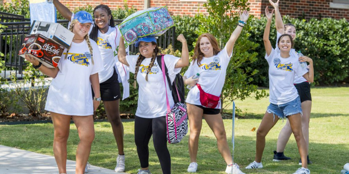 Five students pose in front of a residence hall on move-in day