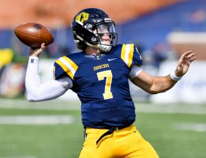 a football quarterback arcs his arm back in preparation to throw the ball