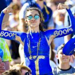 "a girl covered in blue body paint holds up her arms, which say ""boom boom"""