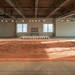 a rug made of red dirt covers the floor