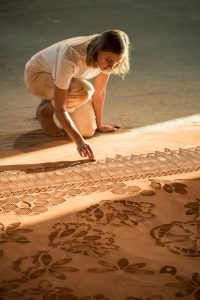 A woman draws in red dirt on the floor.