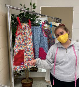 Student stands with completed dresses.