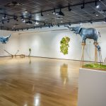 """The """"Flight of the Elephant"""" exhibit in the Melton Gallery features sculptures of elephants of various sizes, including some on stilts or with constructed wings."""