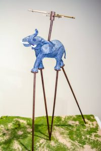 A small scupture of Amelia the elephant walking on stilts