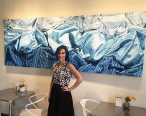 Erica Bonavida stands in front of her painting.