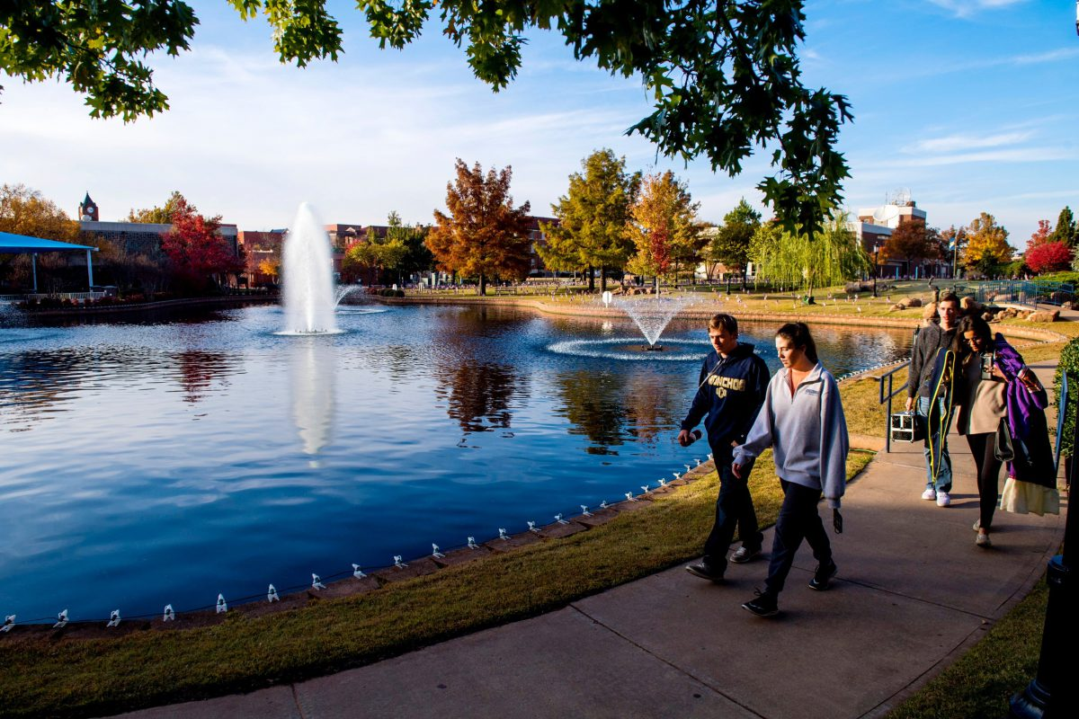 Photo of 2 students walking along Broncho lake