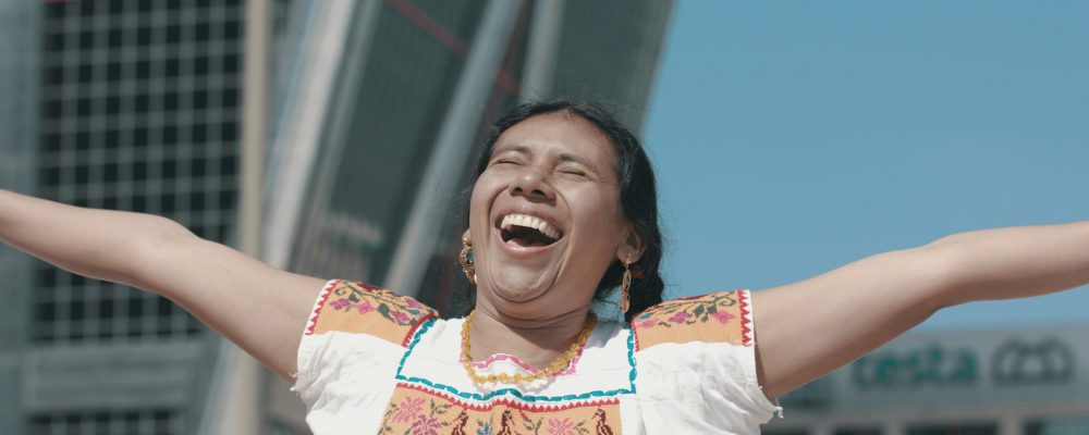 Film still- Indigenous woman with arms raised smiling at the sky