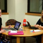 Two students at Chambers library working on a book review