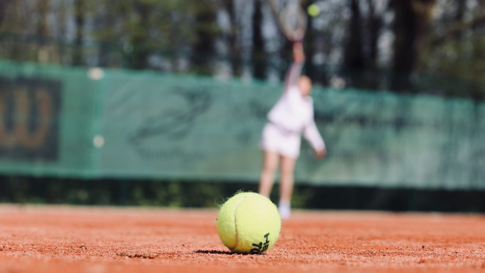 stock photo of tennis ball with blurred player in background