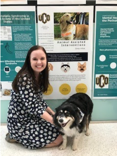Photo of student kneeling with therapy dog in front of research poster