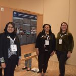 Four students at conference poster