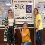"""Photo of three students in front of a """"STLR Location"""" sign at the UCO VSLC"""
