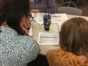 Photo of the back of two people looking at STLR training paperwork