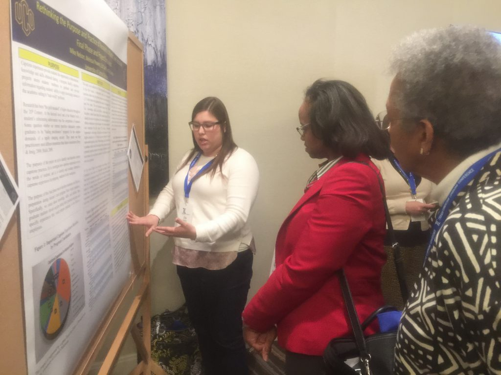 Student explaining poster to two attendees