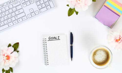 Write a Goal for the New Year in a White Notebook on a White Desktop Next to a Coffee Mug and a Keyboard. Top View, Flat Layout.