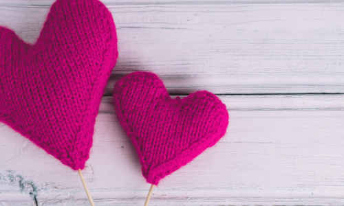 two knitted hearts on a wood background