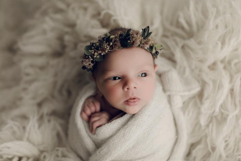 newborn baby girl wrapped in blanket with floral crown
