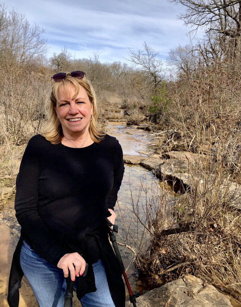 woman posing by a stream while hiking