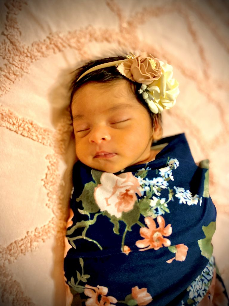 newborn photo of a baby girl wrapped in a floral blanket