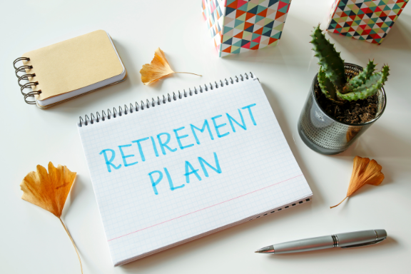 retirement plan written on a notebook with various objects surrounding it