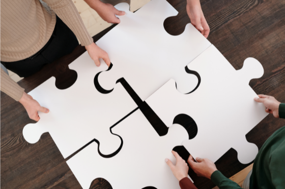 team members holding large puzzle pieces together